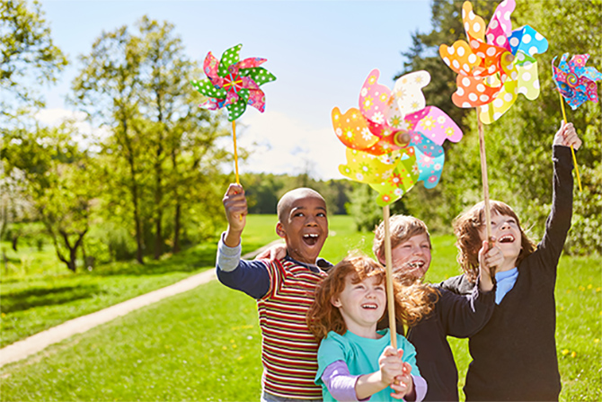 Children as friends celebrate children's birthday in the summer with colorful pinwheels